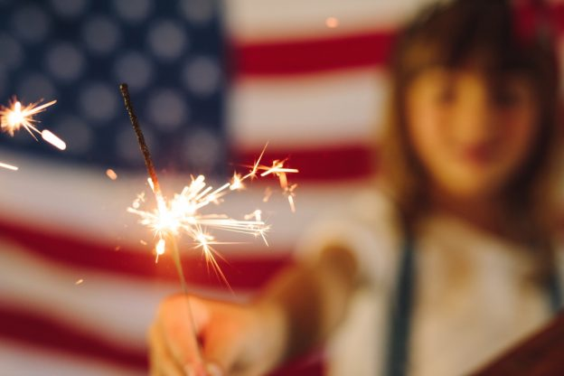 Young woman in front of American flag with sparkler