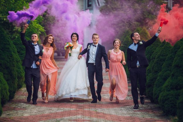 wedding party walk celebrating with purple and red smoke bombs